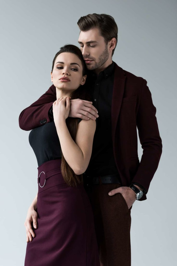 Handsome man embracing his girlfriend, isolated on grey
