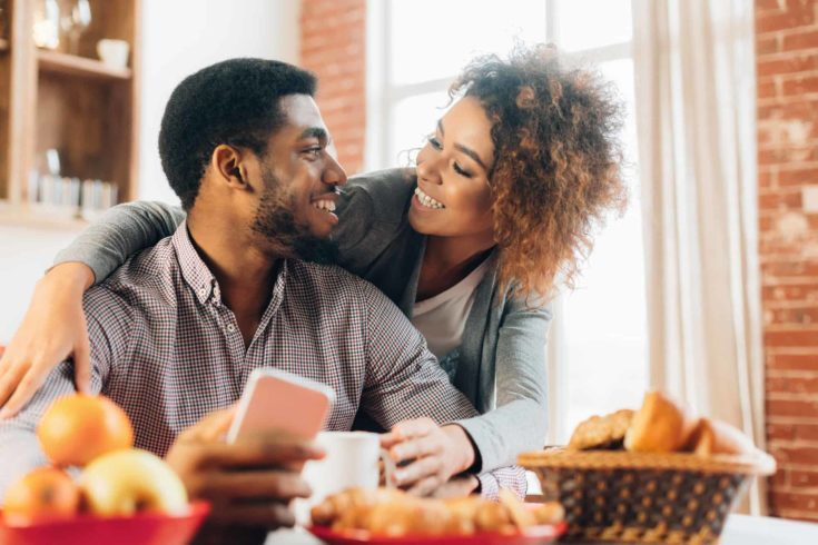 Loving young couple using smartphone in kitchen
