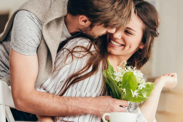 Young couple embracing with bouquet of flowers