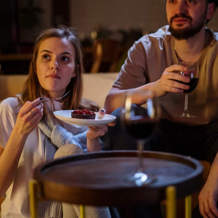 Woman eating cake and man holding a glass of wine