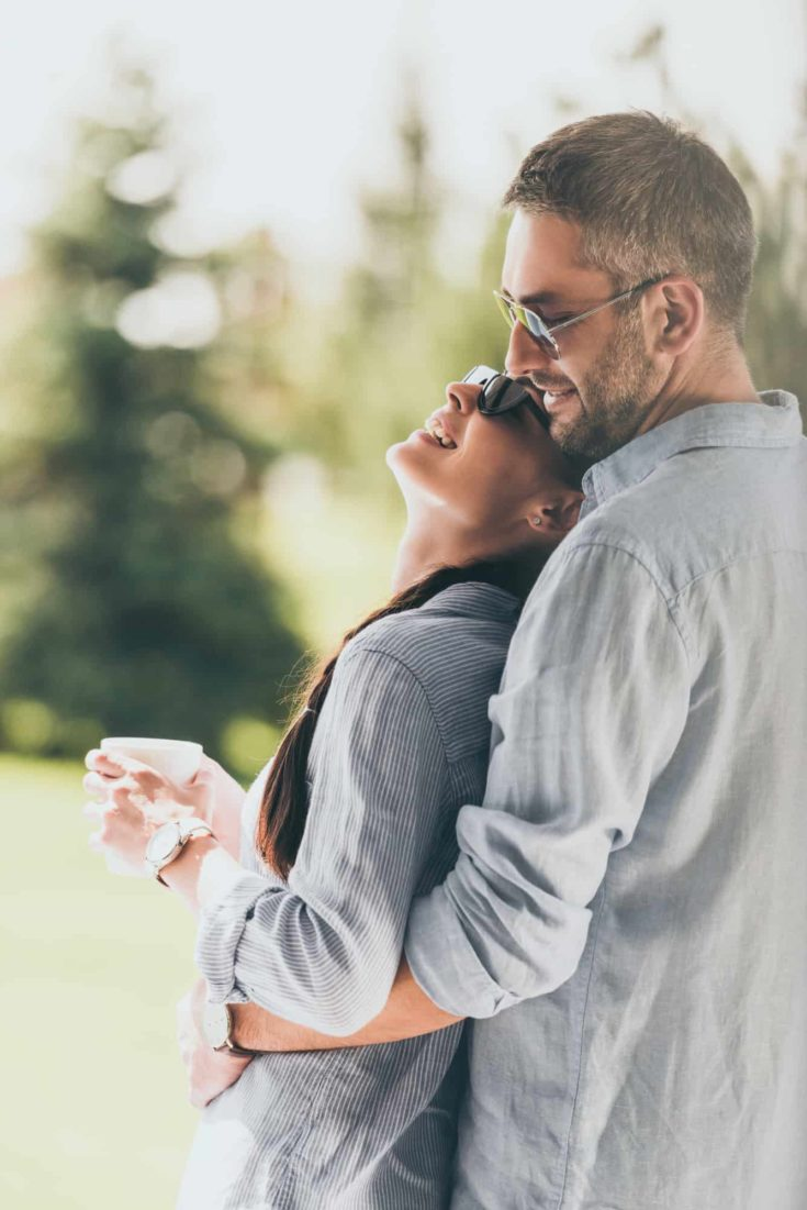 Side view of happy man in sunglasses embracing girlfriend with coffee cup outdoors