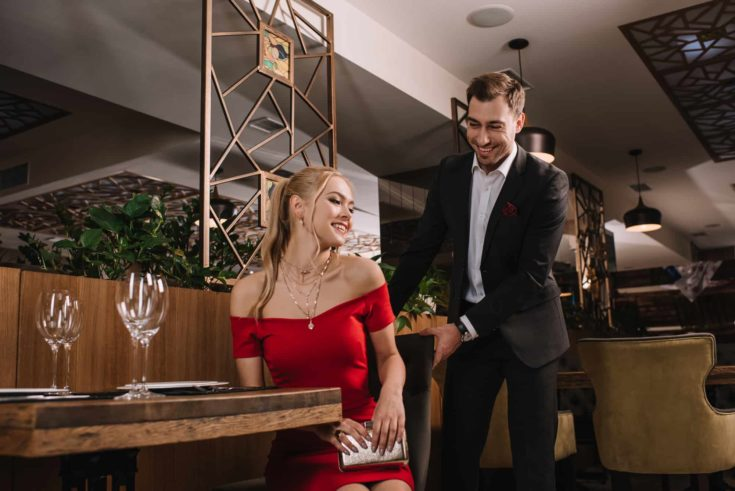 Handsome man helping to sit down attractive woman in red dress