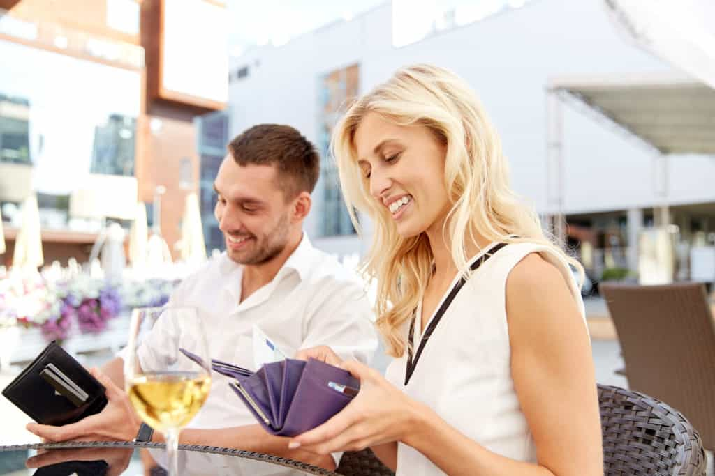 happy couple with wallet and wine glasses paying bill at restaurant