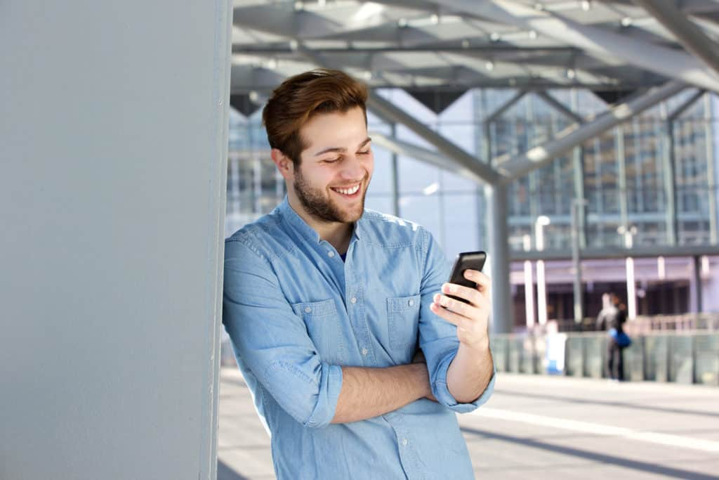 Close up portrait of a smiling man reading text message on mobile phone