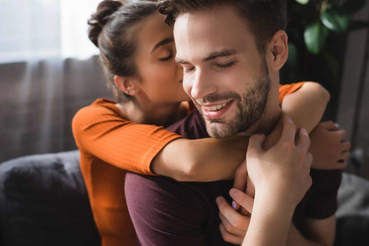 Tender woman embracing happy boyfriend and whispering in his ear