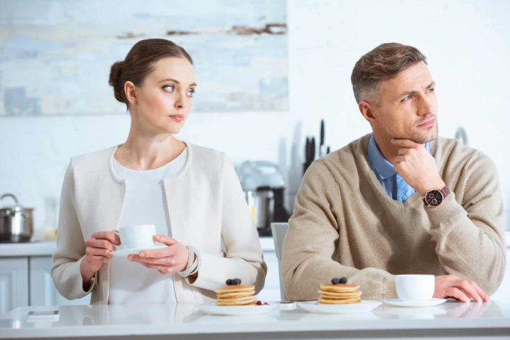 Selective focus of adult man ignoring sad woman during breakfast in morning
