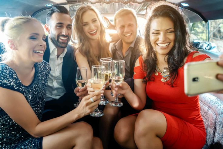 Party people in a limo with drinks taking a selfie with phone smiling into the camera