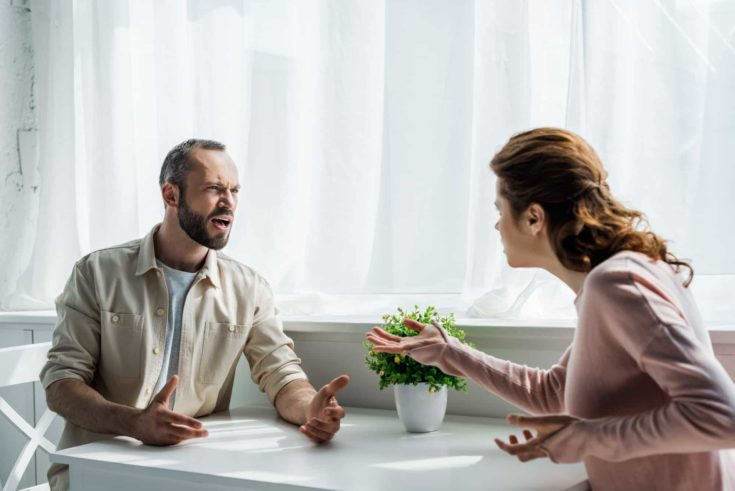 Selective focus of angry man gesturing and looking at woman while sitting at home