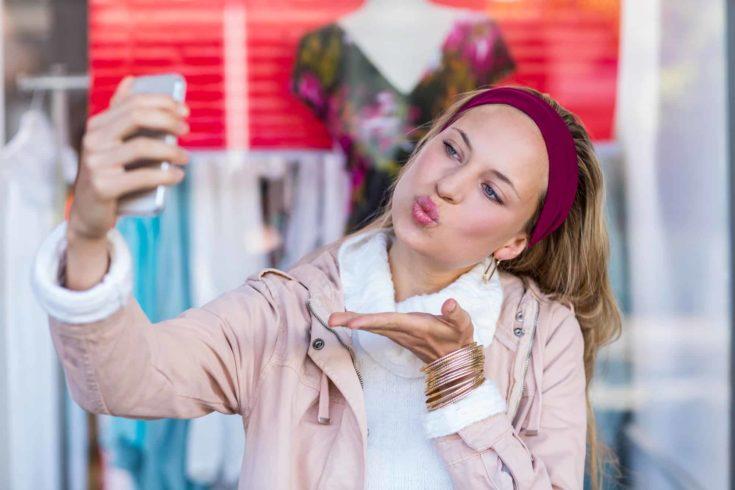 Woman blowing kiss and taking selfies at shopping mall