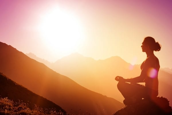 woman meditating on top of mountain