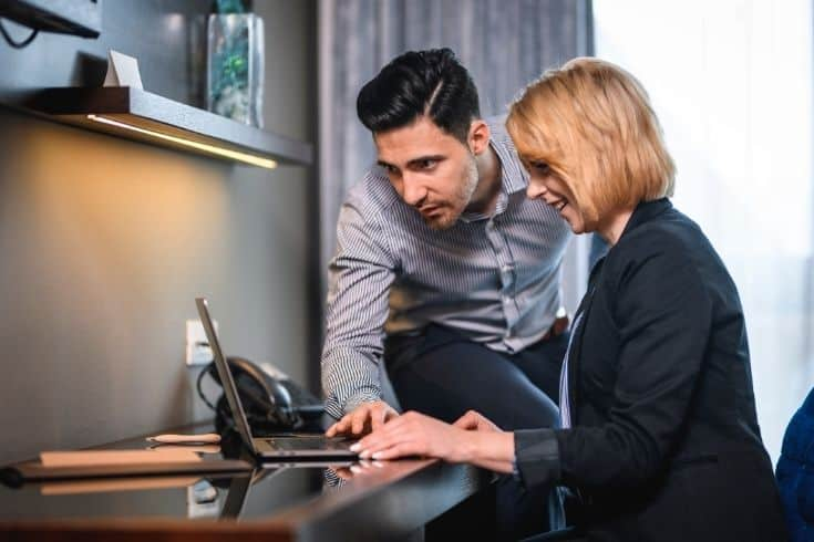 Compatible Businesspeople Working Together in Hotel Room